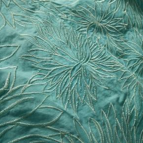 Super fin lysegrøn nederdel fra Karen Millen. Med flot indsyet blomster mønster, der dog har en lille skade.  Nederdelen har indsyet skørt, der giver den et charmerende løft og fylde.