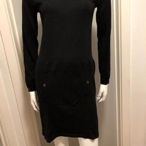Varetype: Strik Farve: Sort Oprindelig købspris: 1899 kr.  Den mest fantastiske bløde kjole i 100% Merino uld. Kradser ikke. Brugt en gang. Små fine messingknapper og lækker kvalitet.