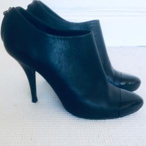 Klassiske sorte Givenchy ankle boots– with a twist. Hæl og bagkappe i bløde svungne former og lak foran på snuden, en fin detalje det sikrer holdbarheden på støvletten. Str hedder 39 men svarer til en 38 med lidt mere plads. Butikspris 4.200kr