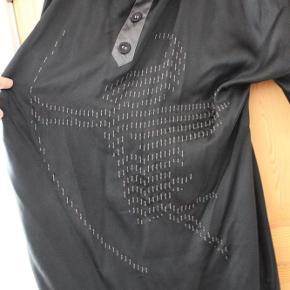 """Varetype: NY tunika kjole i 100% silke m. messing detaljer + broderi tunikakjole silkekjole boheme Størrelse: 44 Farve: sort grå Oprindelig købspris: 850 kr.  ★ NY SMUK HAWALESCHKA SILKEKJOLE M. MESSING- OG BRODERI-DETALJER ★  En rigtig smuk tunikakjole i 100% silke! Kjolen er i sort silke med grå silkekrave og grå detalje på brystet med 3 påsatte silkebetrukne knapper (til pynt - kan ikke åbnes). Nedadtil er med løs tråd """"broderet"""" et grafisk mønster af, hvad der kan anes som værende en figur med bue - måske Amor? Tunikakjolen har store vidde ærmer med aflange runde messing-silke påsyet langs ærmekanterne - en ret speciel detalje! Silken smyger sig let, når man har den på, så den er virkelig behagelig og blød.  Tunikakjolen er en str. 44, men vil kunne passes af både en M og L, og pasformen er vid oversize. På mig selv går den et godt stykke ned over numsen - til midten på lårerne, og jeg er 158 cm høj. 100% ægte silke samt messing. Anvisningen oplyser: Undgå vask eller skånsom rensning.  Tunikakjolen er helt ny og aldrig brugt, og der sidder stadig et mærkat i. Jeg husker dog ikke nypris, men mener den var på ca. 850,-. Skriv emailadresse for billeder i stort format, så du kan zoome ind og se alle detaljerne :-)  ★ PRIS + porto ★  SPAR PORTO og afhent i Esrum, Nordsjælland. Kom også gerne forbi og prøv/se varen ;-)"""
