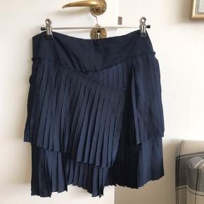 Flot plisseret nederdel med asymmetri foran. Kun brugt 2 gange - har dog sat den som god men brugt, da den er lidt svær at stryge pga alle plisseringerne😉