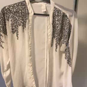 Fin cardigan/skjorte med pailletdetaljer ved skuldrene. Fint og tyndt stof.   Giver mængderabat.