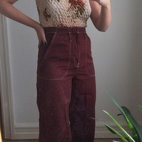 Rødbrune bukser fra Topshop. Størrelse 40, men passes bedre af en størrelse M. Brugt få gange, så i fin stand. Nypris 500 kr.