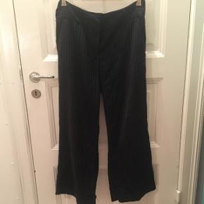 Sorte vide bukser med hvide striber. Der er nogle små huller under knæene på højre ben. Ellers fin stand.