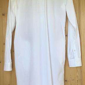 Den flotte skjortekjole er med lommer, flot krave og  har skjult knappelukning. Virkelig skøn skjorte, der kan bruges lukket og åben. Som ses er det en lige ned model. Den sidder så flot.