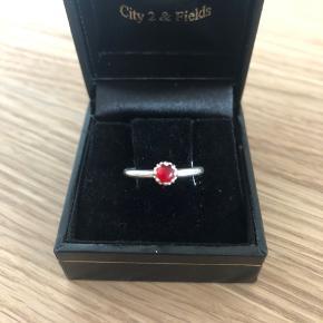 Den sødeste og smukkeste sølv ring med klar rød krystal. Størrelsen er XXS, er designet er de klassiske spinning ringe. Ringene har stempler og ægtheden kan godkendes hos guldsmed  Sender gerne mod forudbetaling ellers kan den beses hjemme hos mig   Æske medfølger ikke