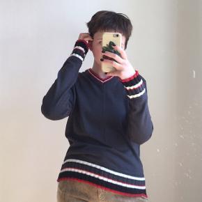 Blå sweater fra mærket Stefano Largo. Den har røde, hvide og sorte striber ved ærmerne og nederste kant. I god stand. Passes af en størrelse S/M. Jeg er selv en størrelse S.