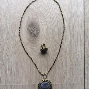 Fin halskæde og ring i bronze (falmet?) og med grå marmoreret sten i midten. Sælges samlet.