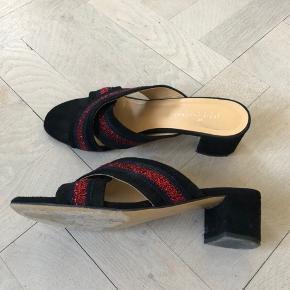 Heartmade ruskinds slippers model Deena med hæl. Sorte ruskind med røde og mørkeblå glimmer detaljer. Skoene har skindfoer og lædersåler. Skoene er brugte og har div små brugsspor. Nypris 2699 kr