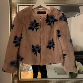 Super blød og fin jakke fra Zara i imiteret pels. Gammel rosa med blå blomster. Rigtig fin stand.