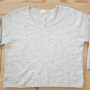"""Lækker blød og tynd strik med lidt uld i. Har """"rullede"""" kanter forneden og ved ærmer (se billede). Måler ca. 60 cm o længden og 2x60 cm i bm. Fremstår næsten som ny 🌸"""