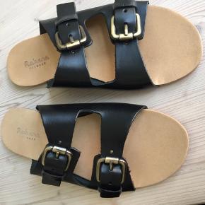 """Super cool sandaler fra Rabens Saloner (""""Stina""""). Sandalerne er i sort skind og lukkes med to remme med justerbar spænder.  Aldrig brugt. Sælger kun og bytter ikke."""