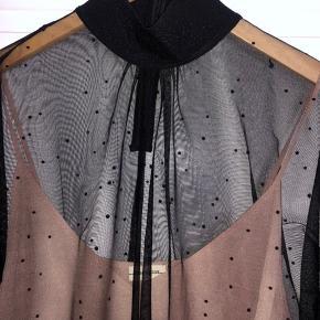 Fin mesh bluse med prikkede detaljer, høj hals, og nude undertrøje. Aldrig brugt.  Bytter ikke.  Køber betaler porto.
