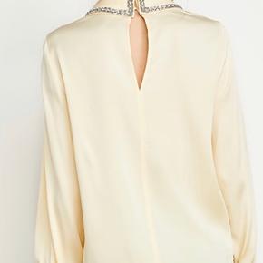 Skjorten er i en fin lys gul med krystal sten på kraven og lange ærmer med stramme manchetter. Blusen lukkes med knapper i nakken og har en fin åbning i ryggen.  95%viscose og 5% elestan