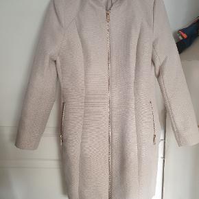 Figursyet lys / sandfarvet /beige strukturvævet  jakke / frakke fra H&M. Str 38. Perfekt overgangsjakke. Sælges ikke i butikkerne mere. 600 kr fra ny.
