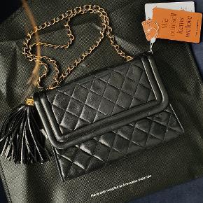 Mindstepris 9300 Overvejer at sælge min Chanel Flap taske med en sød tassel på den ene side, da jeg hellere vil have en anden model.  Sort med 24 carat guldbelægning på hardwaren.  Der er ingen pletter inde i den eller udenpå. Læderet er lam, og er super blød og lækker. Der er MEGET lidt slid på kanterne i bunden. Den er købt på Vestiaire Collective, og jeg har ikke selv brugt den.   Mærkaterne som garanterer taskens ægthed medfølger. Har de originale mærkater, og de mærkater, som jeg fik med, da jeg sendte den ind til Vestiaire Collective i august, for at få den kontrolleret igen. Mål 22x16x6 kæden er ca 46 cm  Sender gerne flere billeder af tasken.  Køber betaler porto og ts gebyr Kan tages med til Ølstykke/København