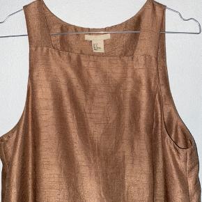 Flot kjole med lommer og folde/slæb-detalje på ryg. Str. 38. Rigtig fin stand. Materiale som har look af råsilke. Farve er en skinnende lysebrun/gylden nuance.
