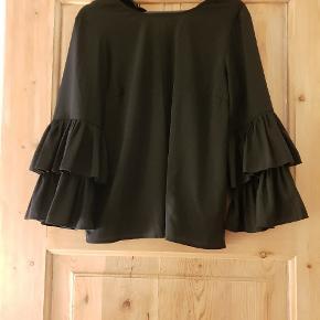 Flot og elegant sort bluse med flæseærmer. Er brugt få gange. Str m, men passer også en s, hvis man som mig også synes, at det er flot løstsiddende.