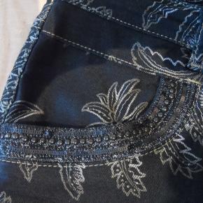 Flotte perledetaljer ved lommer. Stretch stof. Stoffet giver sig ved brug. Meget behagelige at have på.