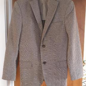 Varetype: mænd blazer Størrelse: 46R Farve: Grå  Detajle og kvalitetsbevidst blazer fra J.Lindeberg, model Patch herringbone soft hopper, slim fit. lavet i primært virgin uld MP 500
