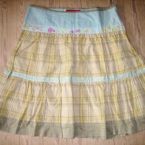 100% ny og ubrugt.Skøn nederdel i etager, med broderi og i ternet bomulds-stof. Taljevidde: 47 cm x 2 Længde: 66 cm.  Ingen byt, og prisen er fast
