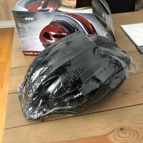 Helt ny cykelhjelm i str. 57-63. Sælger to stk: en i sort og en i sølv. Hjelmene har indbygget spejl, så man kan kigge bagud uden at dreje hovedet.   Pris pr. stk.: 65kr Pris for begge to samlet: 100kr