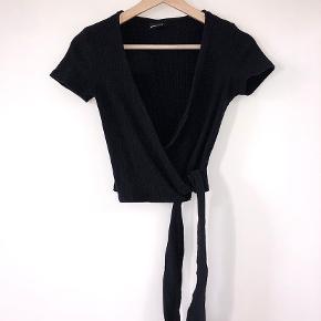 Super fin sort t shirt som kan bindes både foran og bagpå - det kan bindes sådan så den dækker navlen eller bruges som crop top.