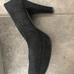 Smukke sko i ruskind med præget slangeskindsmønster. Hælen måler på det højeste sted 10,5 cm. og plateau foran måler 2 cm. Har isat hælebeskyttelse, som kan fjernes. Nypris 1100,- Har aldrig været brugt.