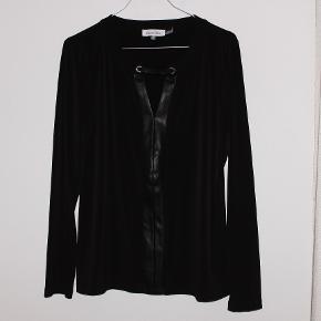 Sælger denne smukke Calvin Klein bluse med læder - og gulddetaljer. Det er en str M, og fejler intet. Sælges da jeg ikke får den brugt. Blusen er i blødt og lækkert materiale. Det er coutur.   Sælges til 175kr.