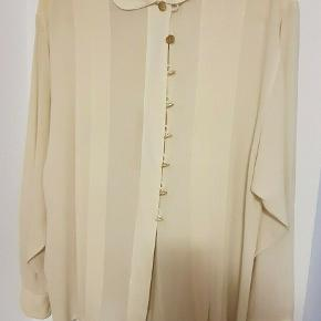 Så smuk vintage skjorte fra Chanel sælges med ikoniske C-logo som knapper - oprindelse er 1980'erne. Skjorten er i fin vintage stand, men naturlige aldersrelaterede brugsspor må forventes. Den har mistet sin ene knap ved halsen. Ingen størrelseslabel i, men den passer henholdsvis en str. S eller M. Jeg har købt den i selvsamme stand i en secondhand shop i Milano i sommers til 2400kr - den sælges til 1300kr afhentet eller plus porto.