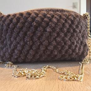 En håndhæklet taske fremstillet af ren Alpakka uld fra Sandnes Garn. Den er udført i en smuk boble-hækling med lynlås-lukning, og er beklædt med hvid bomuld indvendigt, som er slidstærk. Kæden er let, lavet af aluminium.  Farve: Brun Str: 22x15 cm
