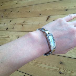 Pænt og elegant smykkeur. Længden af kæden (armbåndet) kan justeres, så det kan sidde til eller løst.  Der medfølger ekstra vedhæng samt købsbevis.  Batteri er dødt.