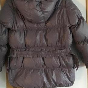Rigtig lækker varm dunfrakke i svag dused lilla. Dun og fjer. Med hætte. Kan knappes af.  Måler fra ærmegab til ærmegab 55 cm. Længden 61 cm. Kan bruges med eller uden elastikbæltet.