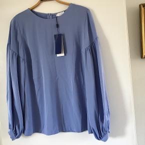 Smuk bluse i smuk lyseblå farve. Vide ærmer og skjult lynlås i ryggen. Style: 2nd Milly.