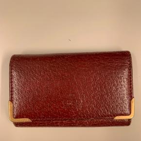 Sælger denne Gucci pung med nøglebærer. Den har en del tegn på slitage som ses på billederne, men fungerer præcis som den skal. Kommer med certifikat og boks