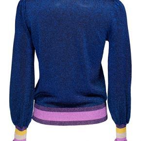 Smuk glimmertrøje i strik med flæseærmer fra Baum und Pferdgarten. Brugt få gange og i perfekt stand.  Normal i størrelsen.