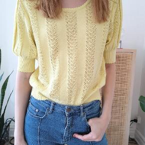 Sød, gul kortærmet strik sweater med pufærmer og fint mønster. Brugt få gange og i god stand.