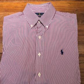 Sælger denne Polo Ralph Lauren skjorte, da jeg ganske enkelt ikke får den brugt. Den er aldrig brugt (kun prøvet et par gange)  Den er købt i USA (sidste år), hvilket betyder at den fitter lidt anderledes end størrelserne herhjemme. Jeg vil vurdere den til at være ca. tilsvarende en stor medium slim fit.  Kvittering haves desværre ikke, men jeg står 100% inde for ægteheden på skjorten. Farven er en hvid/lilla/bordeaux-agtig stribet med en sort hest på brystet.  Skriv endelig, hvis du ønsker at se flere eller bedre billeder. Kan afhentes i Hellerup eller sendes på købers regning.  Tjek evt. mine andre annoncer, hvor jeg bl.a. har mere fra Ralph Lauren. Respekter venligst min pris, da den er fast :-)