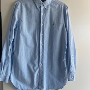 Klar lyseblå Oxford herreskjorte fra Ralph Laurent Classic Fit. Super flot og i meget fin stand. Størrelse 34.