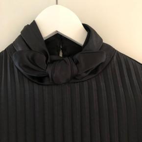 Som ny- kun brugt 1 gang. Købt efteråret 2018. Sort plisseret kjole, går ca. Til knæene. Fine detaljer i halsen og på ærmerne.  Nypris ca. 2400,-
