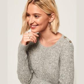 Råhvid smuk sweater med brune nister i, her og der. 😍 Det er i style Croyde; en kabelstrik, som er lavet gennem flere sæsoner hos Super dry. Min er med logoet vævet direkte på strikket, med blåsort tråd. 😉  Se også mine andre annoncer hvis du vil gøre et mængdekup 🥰 Husk at følge min profil 👍❤️