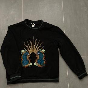 Sort sweatshirt fra hm med print og fine glimmerdetaljer i halsen, ærmerne og kanten. Fitter oversized