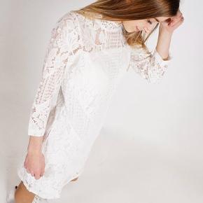Neo Noir konfirmationskjole i off-white blonde med 7/8 lange ærmer.  Lukkes i ryggen med lynlås og en enkel knap i nakken.  Helt ny og ubrugt med mærke og extra knap.  Omkreds bryst 86 cm. Længde 81 cm.  Nypris 700 kr.
