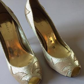 Smukke, smukke vintage guldstiletter med peep toe fra Italienske Vincci med funky rød sål.   Perforeret skind med flammer i guldglimmer. Helt fantastiske!   Perfekt hæl der sidder midt under hælen for optimal komfort. 10 cm.   Brugt enkelte gange men ingen skrammer på hælene eller andre steder.   Ingen æske.   Kan ikke huske np.  Mp 400,- pp ved mobilepay