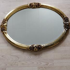 Flot gyldent oval spejl med fin patina. Blomster detaljer i form af udskårne ornamenter.  Spejlet er 80 cm høj og 60 cm bred. Skal afhentes i Grenå.
