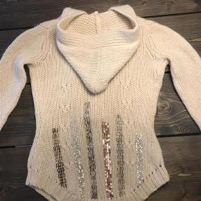 Smuk og varm trøje fra By Malene Birger med hætte og fin pynt på ryggen. 80 % uld, 20 % alpaca. Trøje Farve: Råhvid Oprindelig købspris: 1200 kr.
