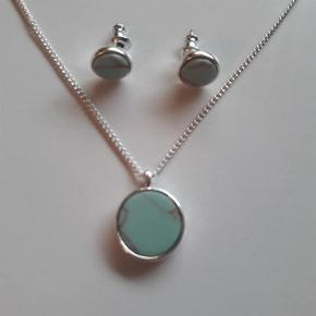 """Ubrugt smykkesæt fra Pilgrim med mintgrønne rostones.  Halskæde og øreringe med mintgrønne marmorerede Rostones. Det har været opbevaret i lufttæt pose og fejler intet.  Halskæden er 40 cm lang og kan forlænges med 9 cm med de ekstra """"huller"""". Vedhænget på halskæden er cirka 1,4 cm i diameter og øreringene 0,8 cm"""