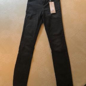 """Sælger disse helt nye bukser - med prismærke på, da de er en smule for lille. De er i en lidt forvasket sort. Bukserne er højtaljede. Modellen hedder """" Molly highwaist superstretch"""" Np: 279 kr. Mp: 220 kr.  Skriv for mere info, eller flere billeder:)"""