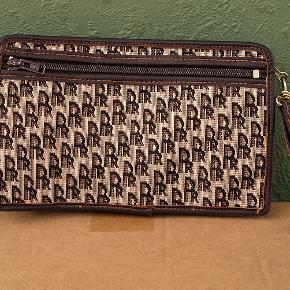Fin lille clutch i vinyl og stof. Indvendig et enkelt rum, udvendig et rum med lynlås bag klappen, og bagtil et rum med lynlås. Lukkes med lynlås. Bredde 22,5 cm og højde 14 og dybde 4 cm. Farve: brun. Materiale: vinyl og stof. Clutchen er ubrugt, fremstår ny, opbevaret korrekt og røgfrit.  Sender gerne, men KUN som MyPack Collect tracebar pakke med Postnord for 35 kr. (benytter IKKE DAO).
