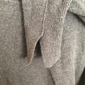 Grå/sort tynd strik med fine detaljer i ærmet.  Farven matcher billede 1